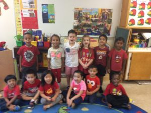 a preschool class in red and white shirts poses together
