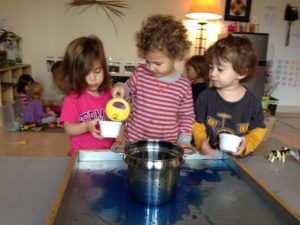 preschool children pouring water into cups