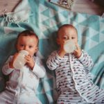 two babies drinking from bottles and laying on a blanket