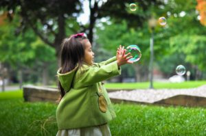 little girl trying to catch a big bubble