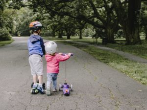 Kids riding scooters at the park