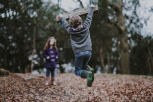kid swinging from a wood swing