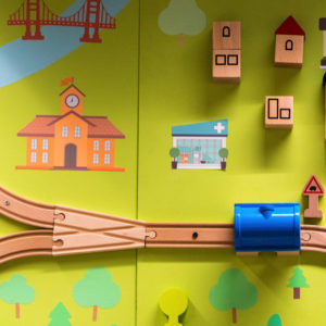Children's train tracks with a picture of a preschool in the background